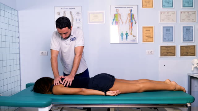 portrait of physiotherapist puts pressure on the back of a patient video