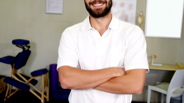 portrait of physiotherapist standing with arms crossed - chiropractor stock videos & royalty-free footage