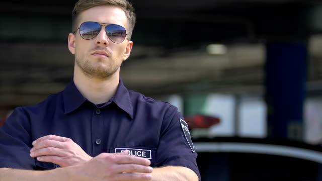 vídeos de stock, filmes e b-roll de retrato do polícia nos óculos de sol que fornecem a segurança e a segurança públicas na cidade - assistente jurídico