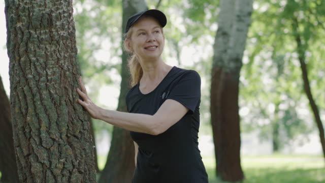 porträt der positiven sportlerin, die sich im sommerpark aufwärmt. lächelnde kaukasische frau streckt beine halten baum an sonnigen tag. aktive dame training im freien an der frischen luft. fitness-konzept. - einzelne frau über 30 stock-videos und b-roll-filmmaterial