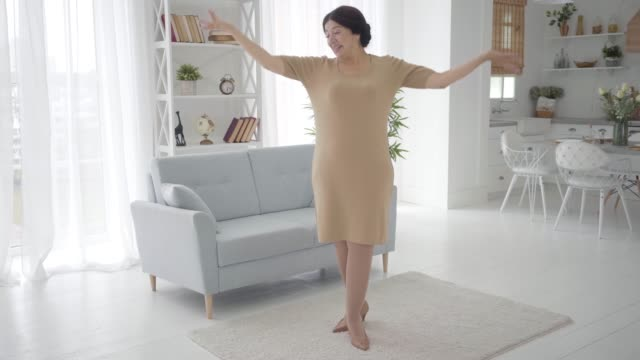 Portrait of positive senior Caucasian woman singing and dancing at home. Cheerful female retiree in elegant beige dress and high-heel shoes having fun indoors. Lifestyle, wealth, happiness, joy.