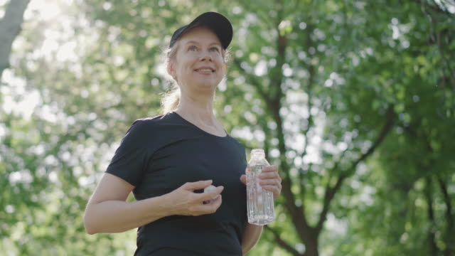 Portrait of positive sportswoman opening water bottle in sunlight outdoors and smiling. Confident slim Caucasian woman in cap and sportswear standing in sunrays in summer park. Portrait of positive sportswoman opening water bottle in sunlight outdoors and smiling. Confident slim Caucasian woman in cap and sportswear standing in sunrays in summer park. one mid adult woman only stock videos & royalty-free footage