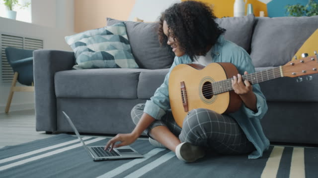 Portrait of pretty Afro-American girl playing the guitar and using laptop at home video