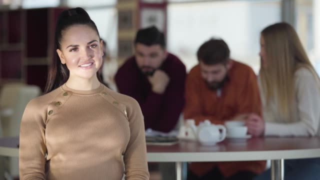 Portrait of pretty brunette Caucasian woman with brown eyes looking at camera and smiling. Positive young girl posing in cafe with blurred friends sitting at the background and talking.