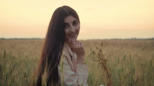 Porträtt av vacker flicka i sommarklänning med vete spikelets i handen. Ung vacker kvinna med charmigt leende video