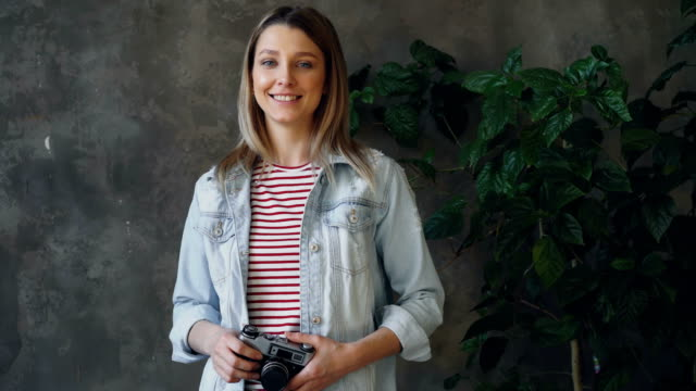 portrait of pretty young blonde standing in loft apartment, smiling happily, posing and looking at camera. she is wearing denim jacket and top and holding camera. - capelli biondi video stock e b–roll