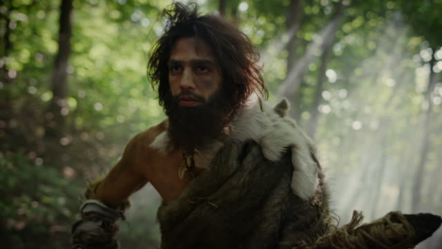 vídeos de stock e filmes b-roll de portrait of primeval caveman wearing animal skin and fur hunting with a stone tipped spear in the prehistoric forest. prehistoric neanderthal hunter ready to throw spear in the jungle - evolução