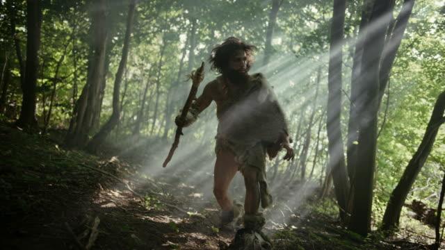 vidéos et rushes de verticale de primeval caveman portant la peau d'animal et la chasse à la fourrure avec une lance de pointe de pierre dans la forêt préhistorique. chasseur primitif de néandertal prêt à lancer la lance dans la jungle - chasser