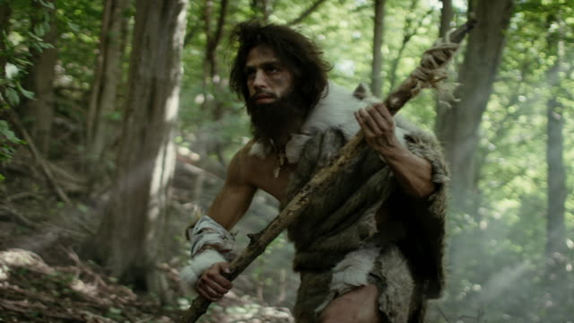 Portrait of Primeval Caveman Wearing Animal Skin and Fur Hunting with a Stone Tipped Spear in the Prehistoric Forest. Prehistoric Neanderthal Hunter Ready to Throw Spear in the Jungle