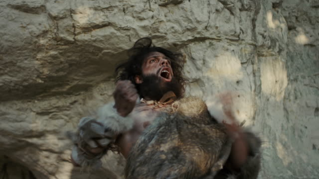 Portrait of Primeval Caveman Wearing Animal Skin Does Aggressive Chest Beating and Screaming, Defending His Cave and Territory in the Prehistoric Forest. Prehistoric Neanderthal or Homo Sapiens Leader