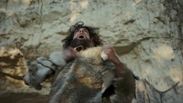 porträtt av primeval grottman bär djurhud hotar bröstet slå och skrika, försvara sin grotta och territorium i förhistorisk tid. förhistoriska neandertalare eller homo sapiens ledare - fornhistorisk tid bildbanksvideor och videomaterial från bakom kulisserna
