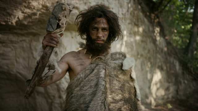 vídeos de stock e filmes b-roll de portrait of primeval caveman wearing animal skin holding stone tipped hammer. prehistoric neanderthal hunter posing with primitive hunting in the jungle. looking at camera - evolução