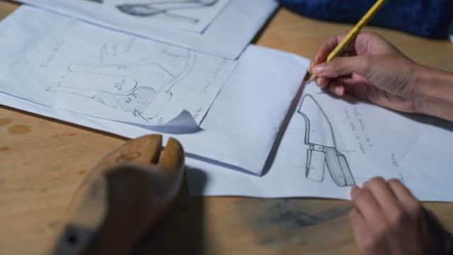 portrait of professional fashion designer drawing a new shoe model according to the italian tradition. - scarpe video stock e b–roll