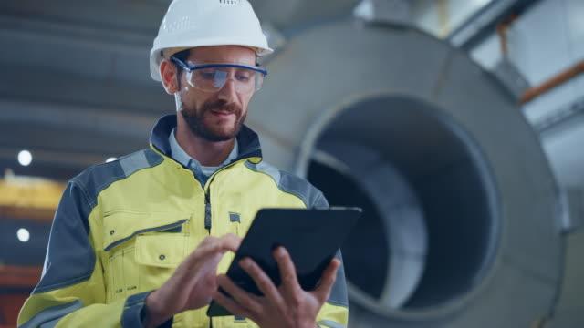 porträtt av professionell tung industriingenjör/arbetare som bär säkerhet uniform och hard hat använder tablet pc. i bakgrunden construction factory för transport pipeline för olja, gas och bränslen - gas bildbanksvideor och videomaterial från bakom kulisserna