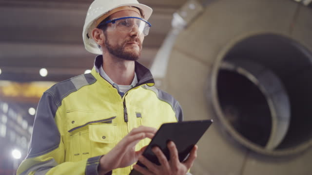 portrait of professional heavy industry engineer / worker wearing safety uniform and hard hat uses tablet computer. in the background construction factory for oil, gas and fuels transport pipeline - attrezzatura industriale video stock e b–roll