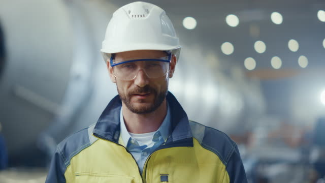 portrait of professional heavy industry engineer / worker wearing safety uniform, goggles and hard hat smiling. in the background unfocused large industrial factory where welding sparks flying - uniform filmów i materiałów b-roll