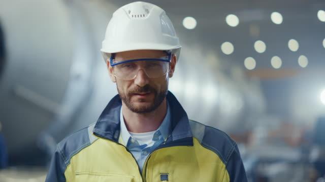 ritratto di ingegnere professionista dell'industria pesante / lavoratore che indossa uniforme di sicurezza, occhiali e elmetto sorridente. sullo sfondo grande fabbrica industriale sfocata dove volano scintille di saldatura - architetto video stock e b–roll