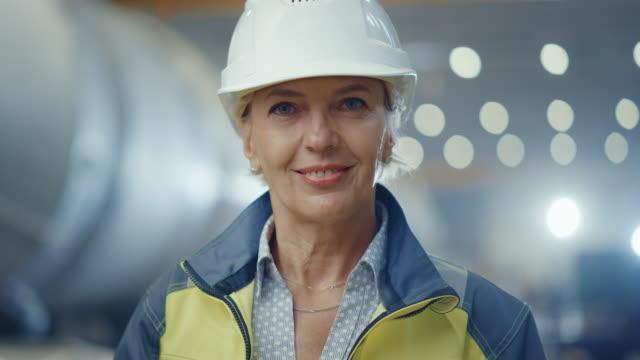 porträt der professionellen schwerindustrie weibliche ingenieur trägt sicherheitsuniform und harten hut, lächelnd charmant. im hintergrund unfokussierte große industriefabrik, wo schweißen funken fliegen - bauarbeiterhelm stock-videos und b-roll-filmmaterial