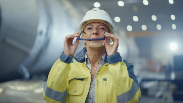 安全ユニフォームとハードハットを着用し、ゴーグルを脱ぐプロの重工業女性エンジニアの肖像画。溶接火花が飛ぶ背景に焦点を当てていない大型産業工場 - 制服点の映像素材/bロール