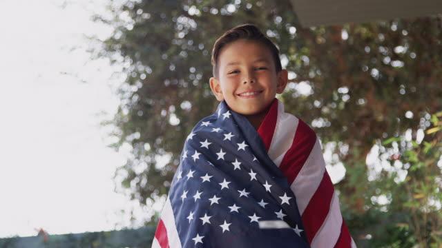 portret dumny latynoski chłopiec owinięty w gwiazdy i paski amerykańska flaga - american flag filmów i materiałów b-roll