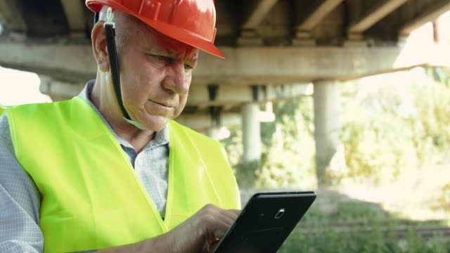 Portrait of railroader checks a railway and types on tablet at camera in summer video