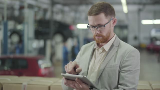 Portrait of redhead Caucasian man in eyeglasses making deal online using his tablet, looking at camera and gesturing yes by shaking head. Car dealership, car business. Portrait of redhead Caucasian man in eyeglasses making deal online using his tablet, looking at camera and gesturing yes by shaking head. Car dealership, car business. salesman stock videos & royalty-free footage