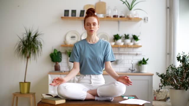 porträtt av avslappnad rödhårig kvinna mediterar medan sitter på skrivbordet hemma på hemmakontoret. - lotusställning bildbanksvideor och videomaterial från bakom kulisserna