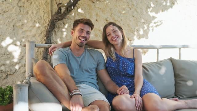 vídeos de stock, filmes e b-roll de retrato de casal jovem relaxado no sofá ao ar livre - sul europeu