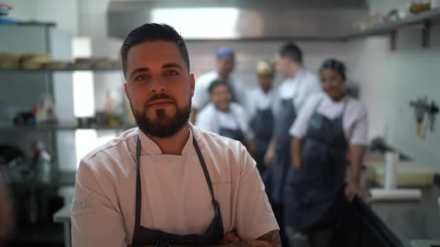 キッチンで彼のチームとレストランシェフの肖像画 - 料理人点の映像素材/bロール