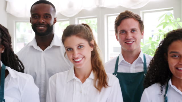 Portrait Of Restaurant Management And Staff Standing In A Line Camera tracks along faces of restaurant staff and management - shot in slow motion wait staff stock videos & royalty-free footage