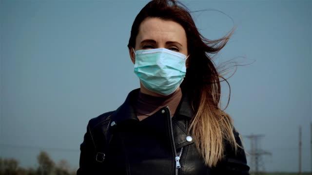 Porträtt av ledsen kvinna i ansiktet medicinsk mask under blå himmel tittar på kameran på frisk luft för att spara från coronavirus video