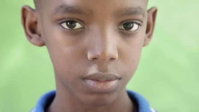 Portrait of sad young black boy looking at camera