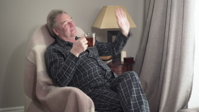 Portrait of satisfied mature Caucasian man waving and showing thumb up out the window. Senior happy retiree sitting in rocking chair at home with cup of tea and smiling. Leisure, resting, lifestyle