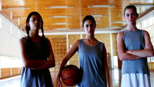 Retrato de colegialas con baloncesto en la cancha de básquet - vídeo
