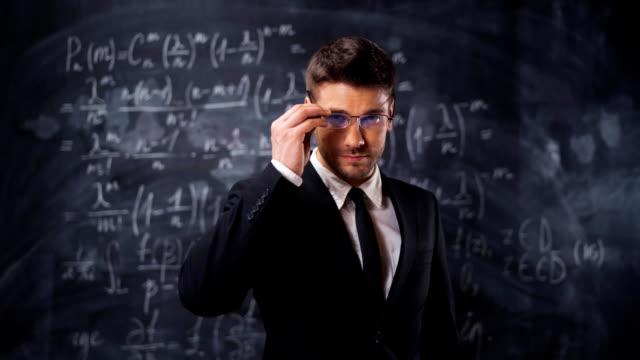 Portrait of scientist man standing near mathematical equations, formula video