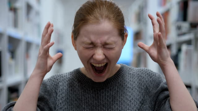 portrait of screaming young woman, shouting in cafe - stress emotivo video stock e b–roll