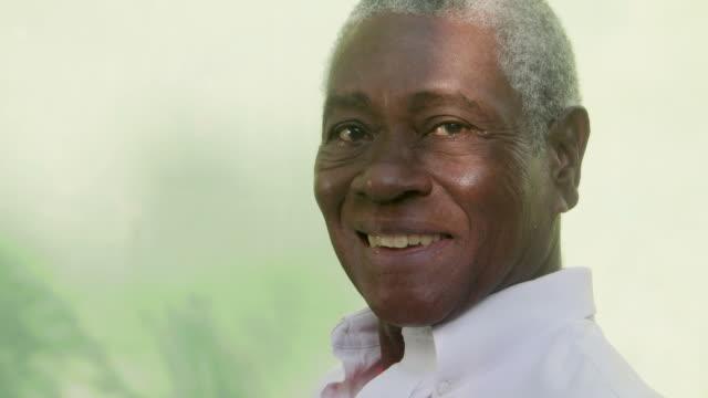 portret starszych czarny człowiek patrzy na kamerę i śmiać się - siwe włosy filmów i materiałów b-roll