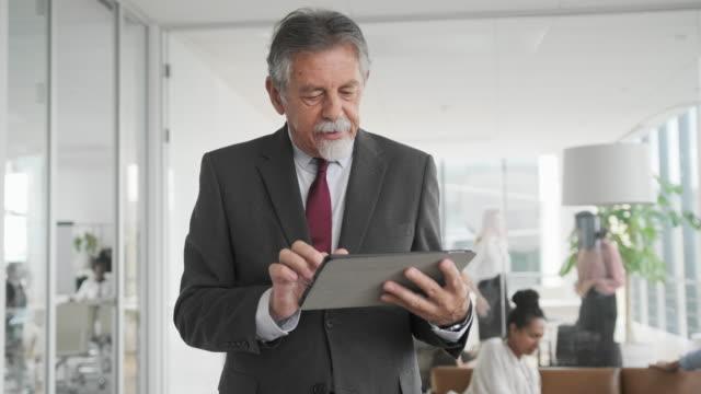 Portrait of Senior Businessman Using Digital Tablet video