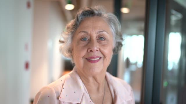 ritratto di imprenditrice senior presso l'ufficio del corridoio - donne anziane video stock e b–roll