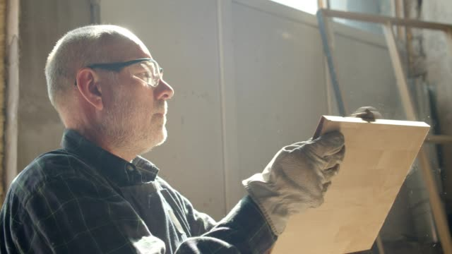 porträt des senior carpenter überprüft die qualität eines holzbrettes in der herstellung. - bauholz brett stock-videos und b-roll-filmmaterial