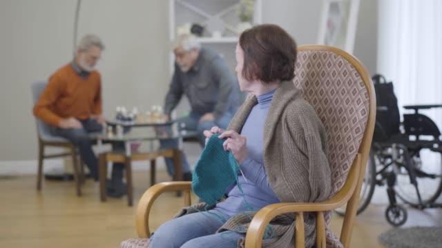 コーカサスの先輩女性が編み物をして、背景でチェスをしている男性を振り返る肖像画。老人ホームでの退職者のライフスタイル。 - community activism点の映像素材/bロール