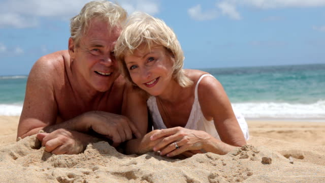 Portrait of senior couple laying in sand at beach HD 1080p:  Portrait of senior couple laying in sand at beach 50 59 years stock videos & royalty-free footage