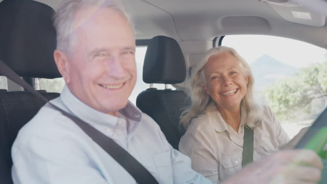 portrait of senior couple sitting in and driving hire car on summer vacation - couple portrait caucasian video stock e b–roll