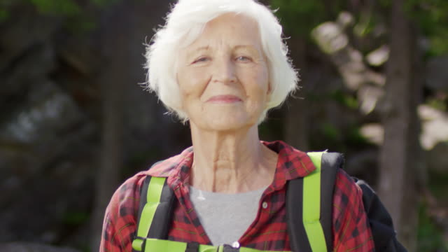 portrait of senior female tourist - woman portrait forest video stock e b–roll