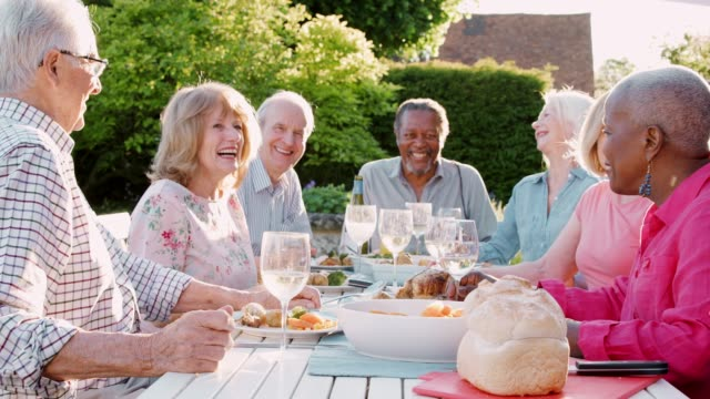 portrait of senior friends enjoying outdoor dinner party at home - couple portrait caucasian video stock e b–roll