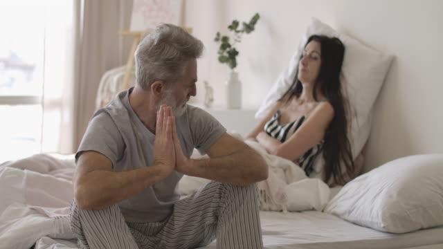 stockvideo's en b-roll-footage met portret van hogere knappe kaukasische mensenzitting op bedrand en het terugkijken van vrouw die bij de achtergrond ligt. volwassen paar dat verhoudingsmoeilijkheden in de ochtend heeft. cinema 4k prores hq. - couple fighting home