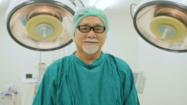 Portrait of senior male surgeon wearing full surgical scrubs smiling camera in operating theater at the hospital. video
