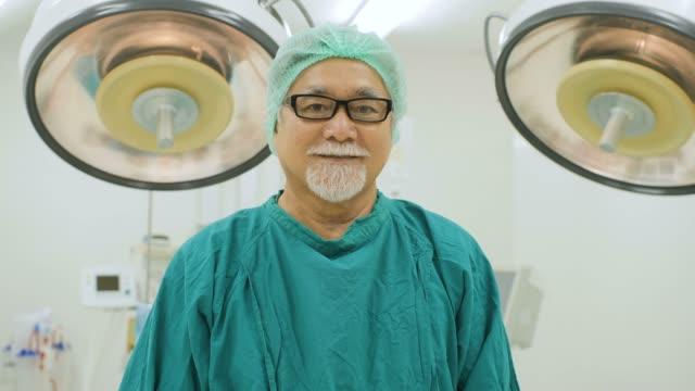 Retrato de sênior masculino cirurgião vestindo avental cirúrgico completo sorrindo câmera em funcionamento teatro no hospital. - vídeo