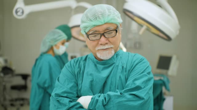 高級男性外科醫生的肖像穿著全手術磨砂微笑相機與工作在醫院的手術室病人的團隊醫師。 - surgeon 個影片檔及 b 捲影像