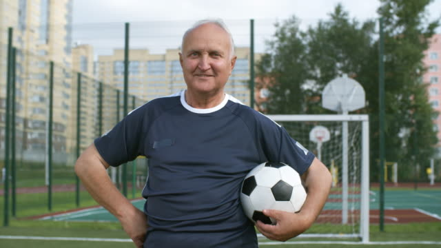 Portrait of Senior Man Holding Football Medium shot of optimistic retired man in blue t-shirt standing on outdoor football field, holding football and smiling at camera sportsperson stock videos & royalty-free footage
